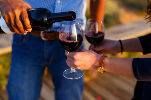 man pouring red wine to friend