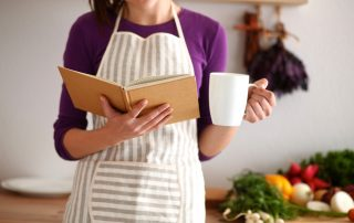 A woman reads a cookbook in her left hand while holding a coffee mug with her right hand.