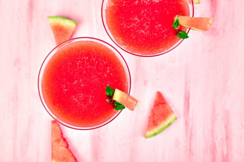 A top down shot of two glasses of watermelon daquiris. Several watermelon slices can be seen on the surface beneath them.