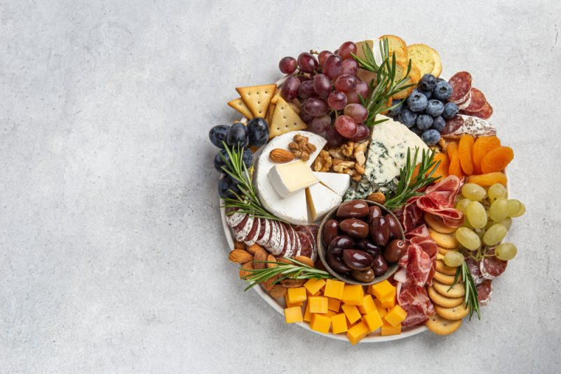 A top-down view of a charcuterie board on a white surface. You can see various types of crackers, cheeses and meats on the board, as well as several assortments of grapes and blueberries.