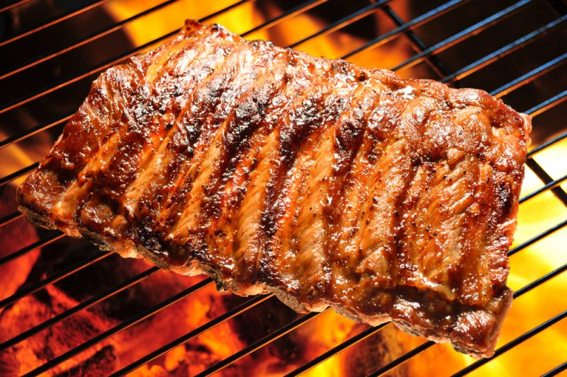 A top down view of a rack of ribs being cooked over a grill.