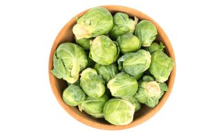 A top down view of a wooden bowl filled with Brussel sprouts on a white surface.