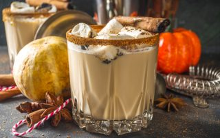 A closeup of a glass filled with pumpkin spice white Russian. It's garnished with marshmallows and surrounded by pumpkins and squash.