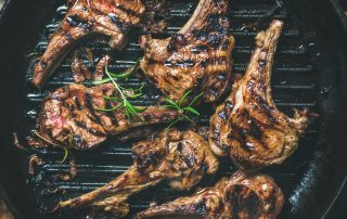 A top down view of six grilled lamb chops over a black grill.